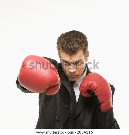 Caucasian mid-adult man wearing suit and punching with boxing gloves