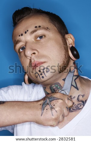 mid-adult man with tattoos and piercings holding knife to throat