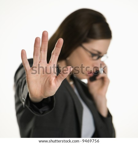 Caucasian mid adult professional business woman talking on cell phone holding hand out to stop viewer.