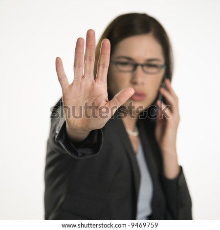 Caucasian mid adult professional business woman talking on cell phone holding hand out to stop viewer. viewer.