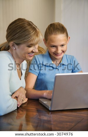 Caucasian mid-adult woman and pre-teen  girl using laptop computer. - stock photo