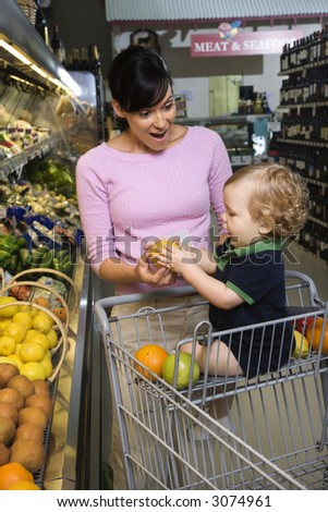 Caucasian mid-adult woman grocery shopping for fruit with young male toddler.