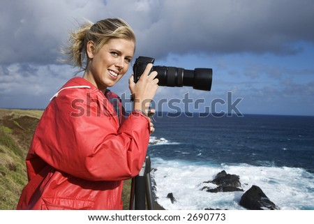 Caucasian mid-adult woman holding camera on tripod, looking at viewer, on cliff overlooking ocean in Maui, Hawaii.