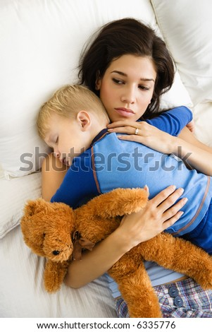 Caucasian mid adult woman holding sleeping toddler in bed.