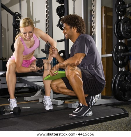 Caucasian mid-adult woman lifting weights while African-American male trainer watches.
