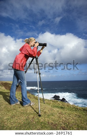 Caucasian mid-adult woman looking through camera on tripod on cliff overlooking ocean in Maui, Hawaii. - stock photo
