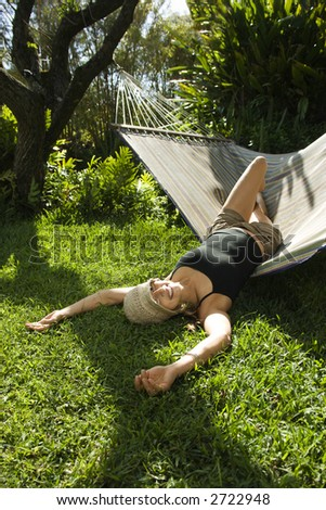 Caucasian mid-adult woman playing on hammock.