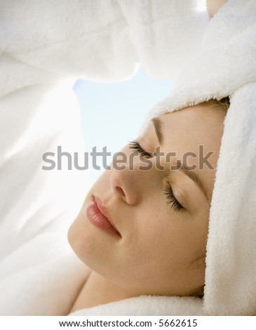 Caucasian mid-adult woman wearing towel on head with eyes closed relaxing.