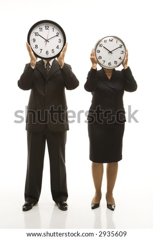 Caucasian middle-aged businessman and Filipino businesswoman holding clocks in front of their heads standing against white background.