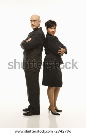 Caucasian middle-aged businessman and Filipino businesswoman standing back to back with arms crossed looking serious.