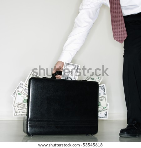 Caucasian middle aged businessman carrying briefcase overflowing with money.