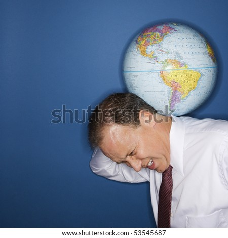 Caucasian middle aged businessman carrying world on shoulders straining.