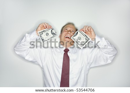 Caucasian middle aged businessman holding hudred dollar bill ripped in half laughing.