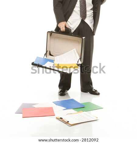 Caucasian middle-aged businessman holding open briefcase with papers falling out.