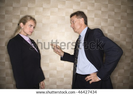 Caucasian middle-aged businessman pointing to and reprimanding mid-adult Caucasian businesswoman. Horizontal format.