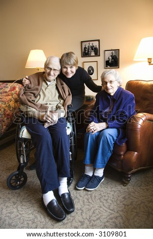Caucasian middle-aged daughter with elderly parents in retirement community center.