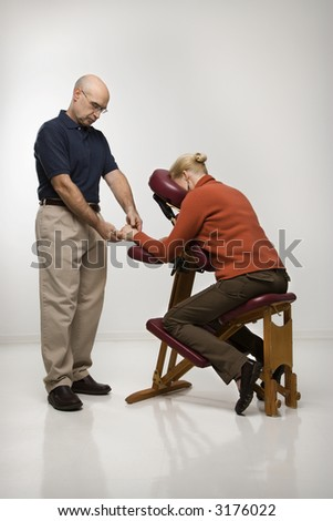 Caucasian middle-aged male massage therapist massaging hands of Caucasian middle-aged woman sitting in massage chair.