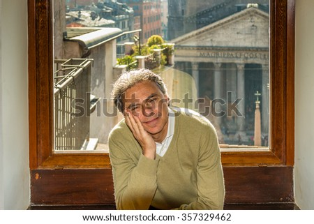 Caucasian middle-aged man with romantic and dreamy expression  with his head resting on one arm looks reassuring having as background a window overlooking the palaces of Rome #357329462