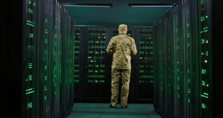 Caucasian military male officer coming in the server room with tablet device in hands, working with secret data and anti-terrorism information. Cybersecurity concept.