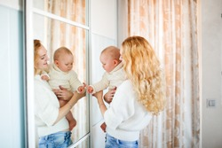 Caucasian mother, a blonde with a baby, examine their reflection in the mirror in the bedroom, the earlier development of baby, child's interest in mirror and reflection. Motherhood