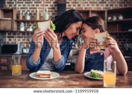 caucasian mother and daughter holding sandwiches and looking at each other in the kitchen