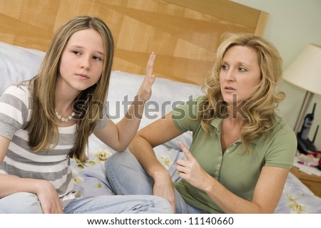 Caucasian mother and preteen daughter arguing while setting on bed an master bedroom - stock photo