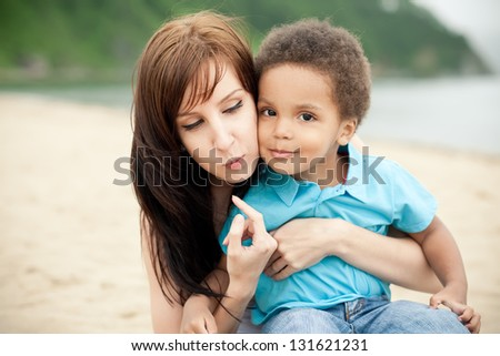 Caucasian mother with a son of an african descend having fun together outdoors.
