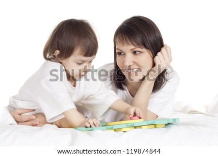 Caucasian mother with her daughter play with a mat in the bed