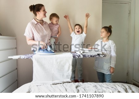 Caucasian mother with two emotional sibling children with an iron ironing linen on an ironing board, mother's assistants. Children help mom in household chores, ironing