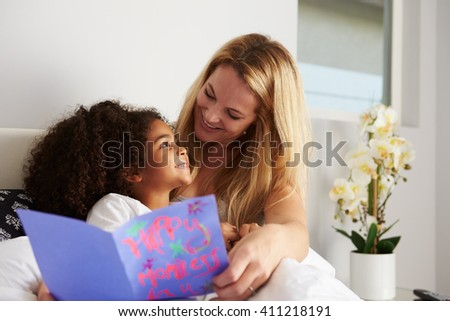 Caucasian mum and black daughter, looking at each other #411218191