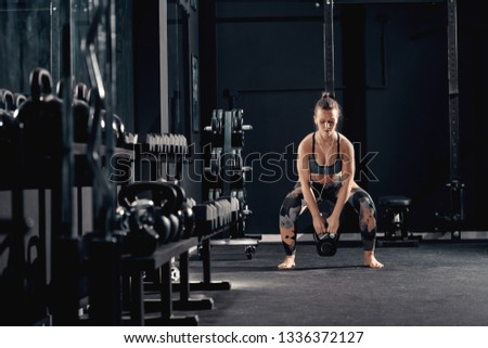 Caucasian muscular brunette with earphones in ears doing workouts with kettlebell in squat position. Night workout in gym concept. #1336372127