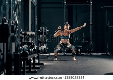 Caucasian muscular brunette with earphones in ears doing workouts with kettlebell in squat position. Night workout in gym concept.