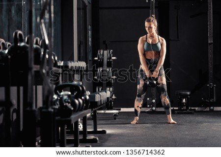 Caucasian muscular brunette with earphones in ears doing workouts with kettlebell. Night workout in gym concept.