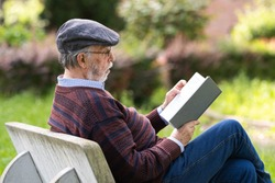 Caucasian old man reads a book on the park bench. Concept of serene old age.
