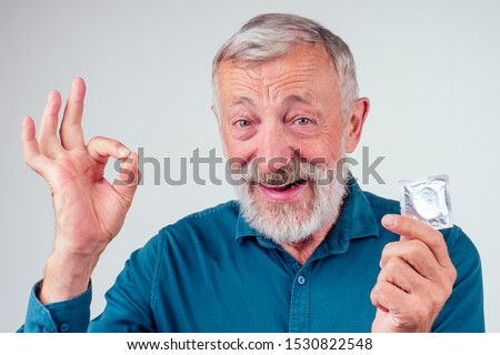caucasian old senior man holding packed rubber latex condom in studio white background.