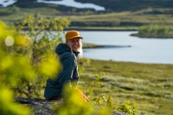 Caucasian outdoor active young adult woman sitting on Rock With outdoor hiking cloths jacket and cap smiling and looking at camera with montain and lake background in Padjelanta national park, Sweden.
