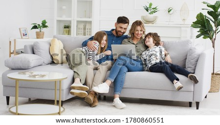 Caucasian parents with kids on couch using gadget. Young man and woman with son and daughter spending time together with laptop. Father and mother watching something online on computer. Rest at home.
