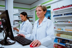 Caucasian pharmacist searching for scripts on desktop computer standing behind counter in pharmacy