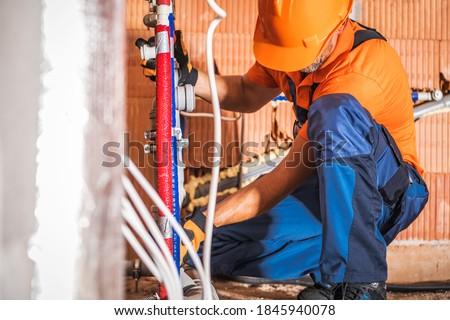Caucasian Plumber Wearing Orange Hard Hat Installing Bathroom Water Supply Inside Newly Developed Concrete Blocks Building. Construction Site Theme.