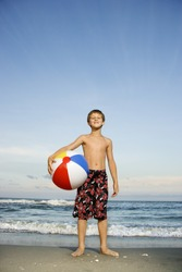 Caucasian pre-teen boy holding beachball on beach.