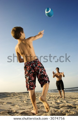 Caucasian pre-teen boy throwing football to mid-adult male.