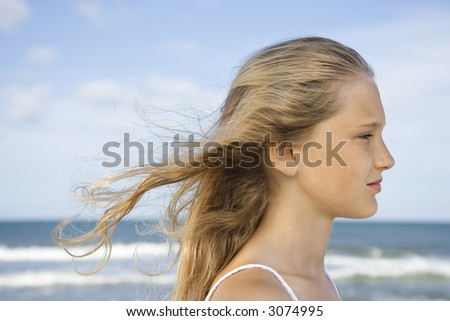 Caucasian pre-teen girl on beach with hair blowing in wind.