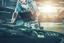 Caucasian Professional Automotive Mechanic in His 40s Making Documentation Inside Authorized Dealership Service Center. Vehicles Scheduled Maintenance.