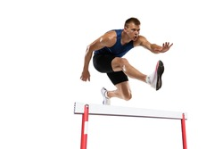 Caucasian professional male athlete jumping over the barrier isolated on white background. Running with obstacles concept. Muscular man. Action, motion, healthy, sport and lifestyle. Copyspace for ad.