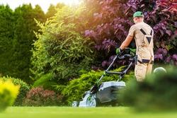 Caucasian Residential Garden Worker in His 40s Trimming Backyard Lawn Using Electric Cordless Grass Mower. Landscaping and Gardening Industry Theme.
