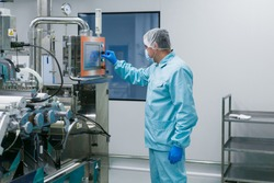 caucasian scientist in blue lab suit configures control panel in big clean room