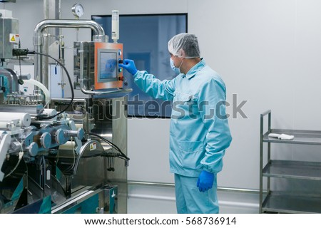 caucasian scientist in blue lab suit configures control panel in big clean room