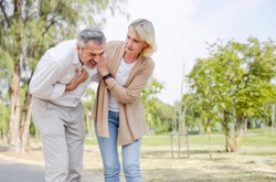 Caucasian senior man suffering, clutching and having chest pain cause from heart attack while walking in the park with his wife, older woman care and support husband, health problem and insurance