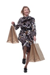 Caucasian senior woman walking with shopping bags smiling at viewer