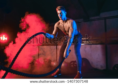 Caucasian shirtless athlete practicing Battle Rope Exercise, great for improvement of Athletic Training, Fat Loss, Core Training, Muscular and Cardiovascular Endurance. Smoky background
